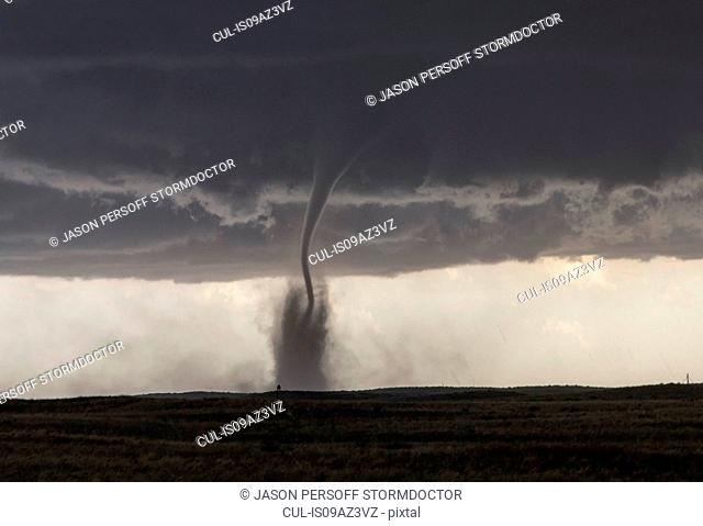 A fine tornado dances within a cloud of dust that moves in ringlets up the lower half of the tornado