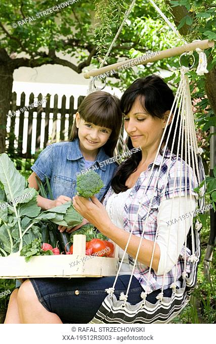 Mother with daughter looking at fresh veggies in the garden