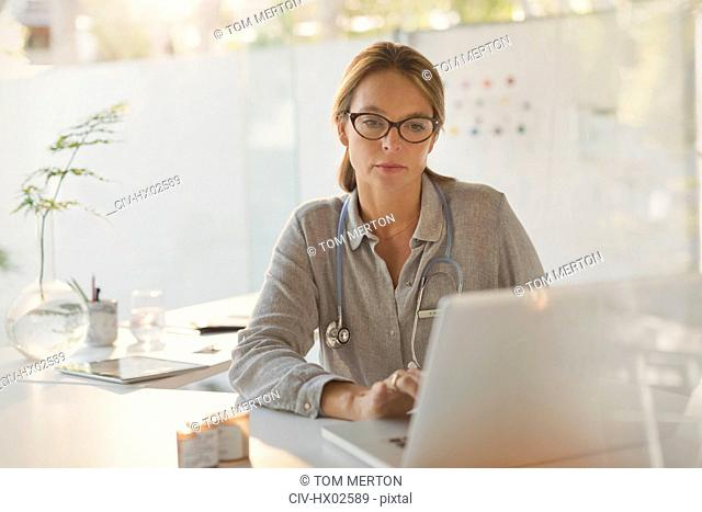 Focused female doctor working at laptop in doctor's office
