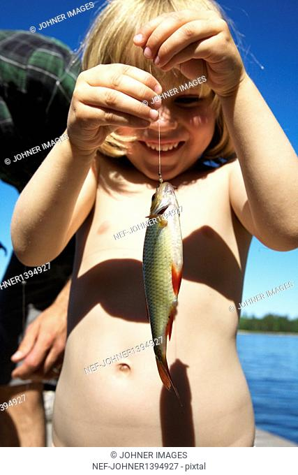 Girl holding fish on hook
