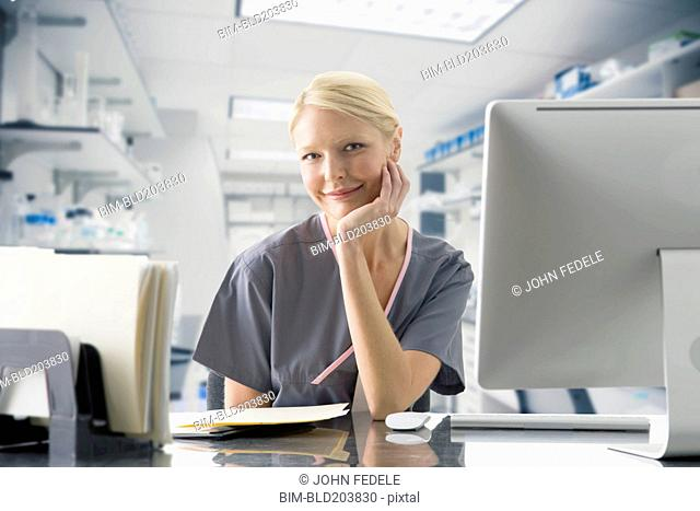 Caucasian nurse working at computer in hospital