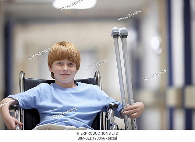 Boy in wheelchair holding crutches
