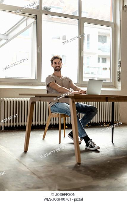 Portrait of smiling young man working on laptop in a loft