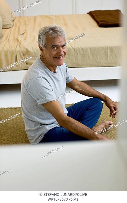 Mature man doing yoga in bedroom