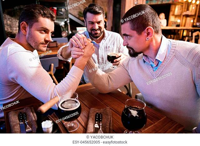 Entertainment for men. Handsome brutal strong men sitting at the table and confronting each other while armwrestling