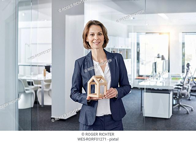 Portrait of smiling businesswoman holding architectural model in office