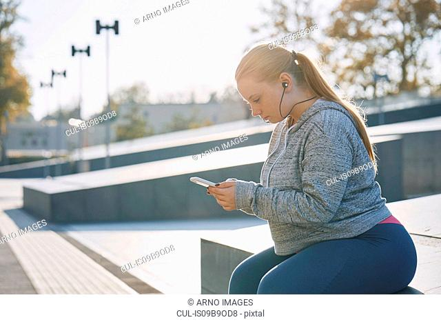 Curvaceous young woman training, sitting on wall looking at smartphone
