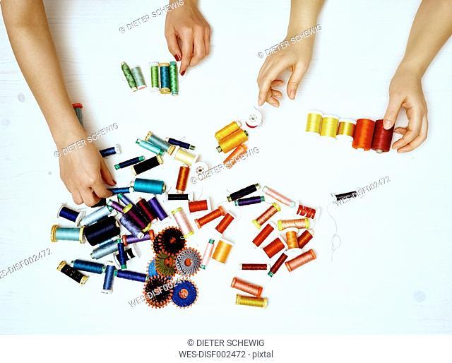 Hands sorting sewing utensils
