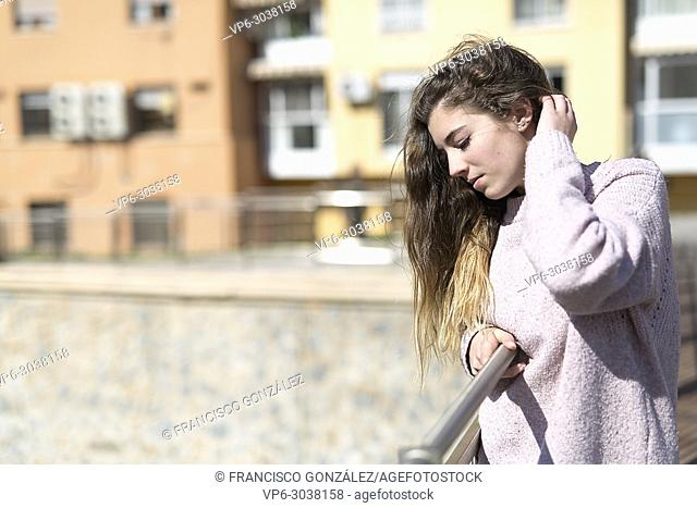 Teen girl resting on a railing in the Spanish city of Orihuela. Horizontal shot with natural light