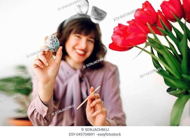 easter hunt. beautiful stylish girl in bunny ears smiling and painting easter eggs on rustic table with tulips and paint in home with space for text