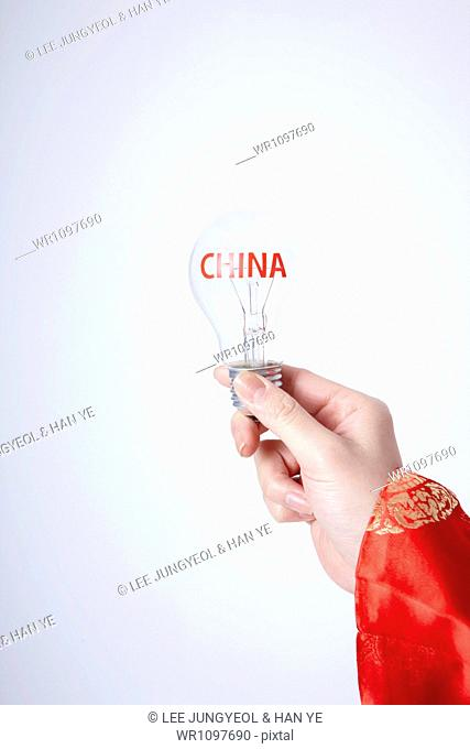 a person with traditional costume holding light bulb with china word
