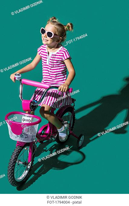 Carefree girl riding bicycle on green background