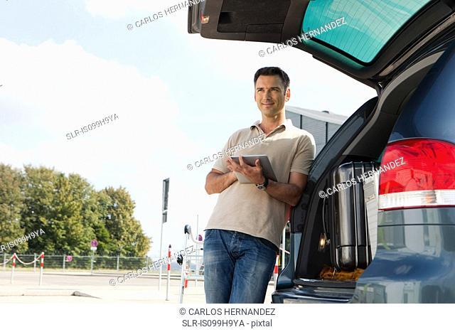 Man using data tablet in airport carpark