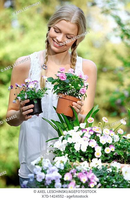 woman working in garden holding flowers in hands