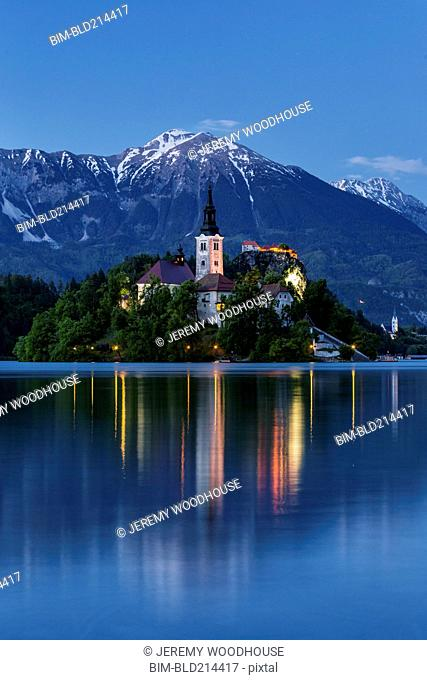 Church tower and mountains reflecting in still lake