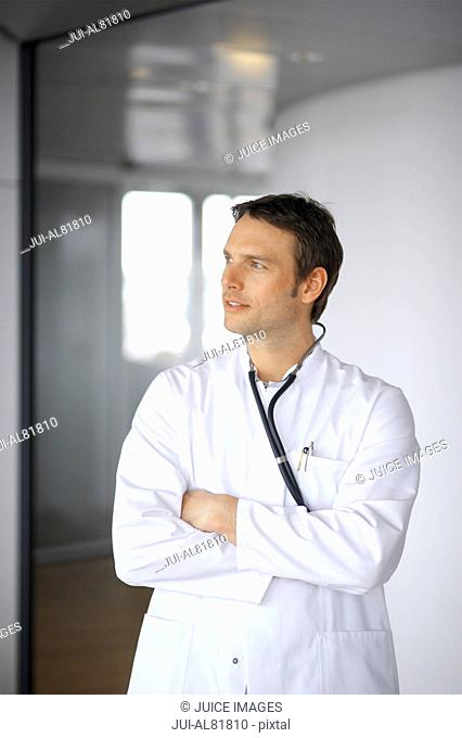 Male doctor with arms crossed looking to side