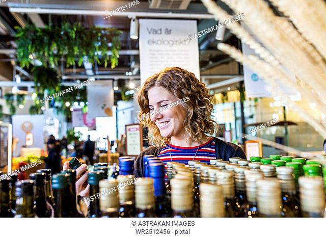 Happy young woman shopping in supermarket