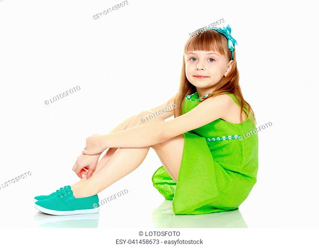 A little girl with long blond hair and a short bangs, in a short summer dress.The girl is sitting on the floor with her hands clasped around her knees