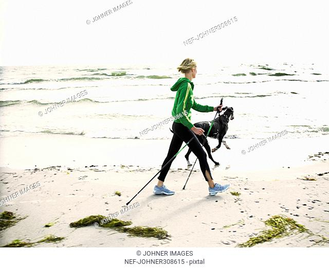 A woman and a dog on the beach