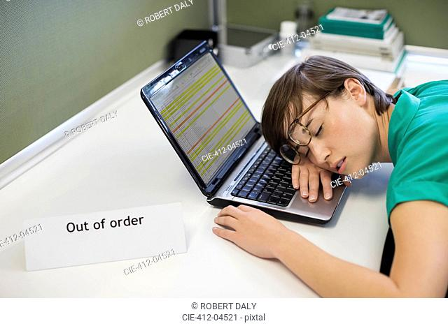 Businesswoman sleeping on 'out of order' laptop