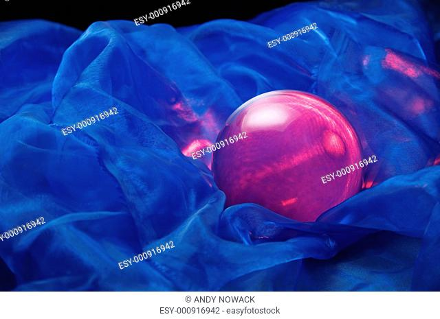 red glass ball on blue