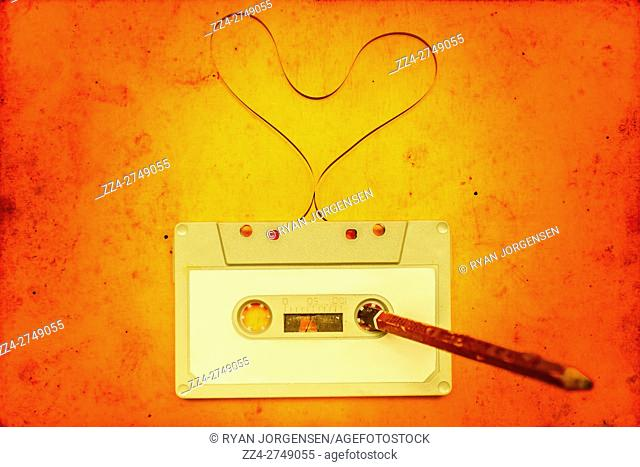 Unwound tape from an audio cassette forming a symbolic heart shape on a vivid orange background with centered yellow gradient and a pencil stuck in the spool