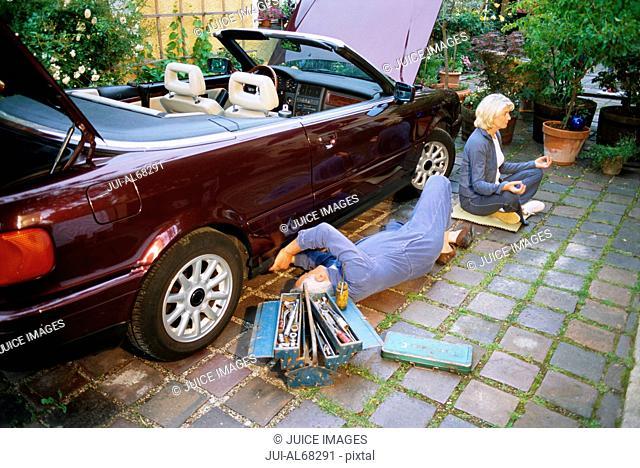 Mature man fixing car, woman doing yoga