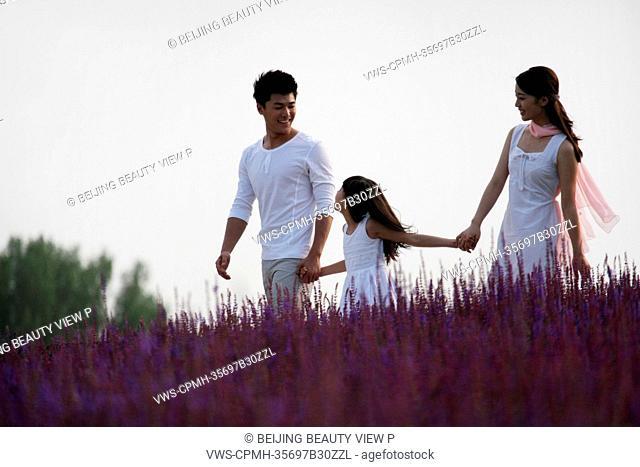 Oriental family standing in lavender garden