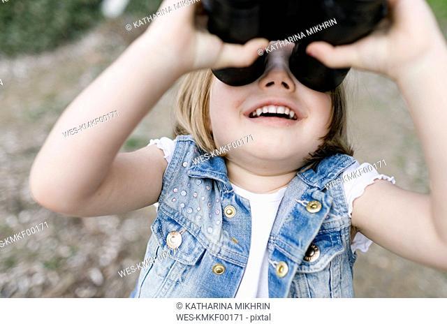 Happy little girl using binoculars