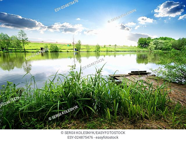 Wooden fishing pier in green grass on river