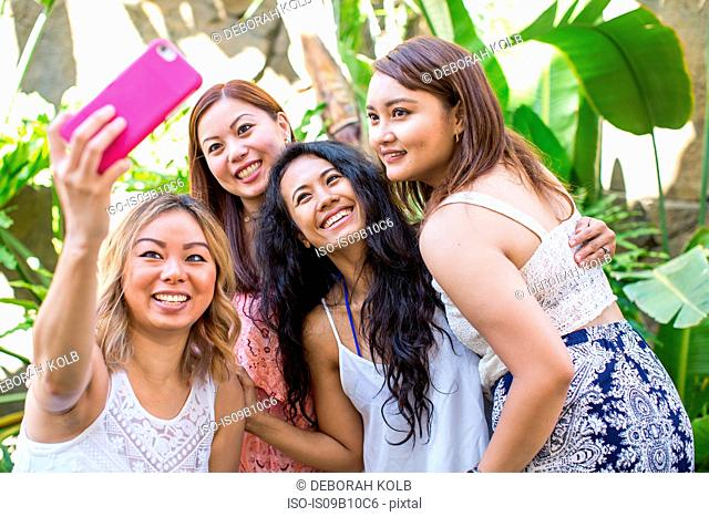 Four adult female friends taking smartphone selfie in garden