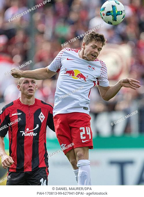 Dorfmerkingen's Fabian Weiss (L) and Leipzig's Dominik Kaiser vie for the ball during the German Football Association (DFB) Cup first-round match between...