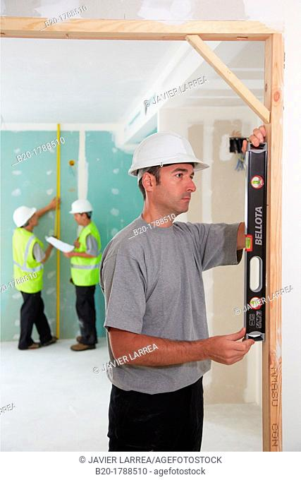 Worker with protective equipment, PPE, Leveling reframe door, housing construction, level, Basque Country, Spain