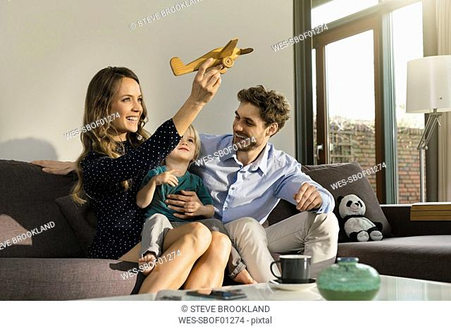 Happy parents and son playing with wooden toy plane on sofa at home