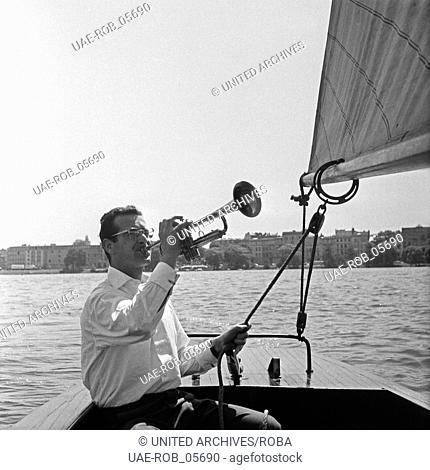 Der Schweizer Musiker, Sänger und Orchesterleiter Hazy Osterwald packt bei einem Segeltörn seine Trompete aus, Deutschland 1950er Jahre