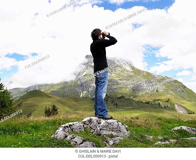 Man looking through his binoculars