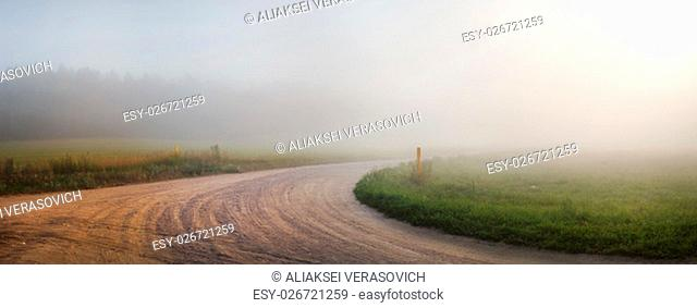 Landscape with an old gravel road in the fog. Turn of gravel road. Panoramic shot. Toned image