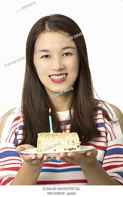 Beautiful Asian woman holding a birthday cake isolated on a white background
