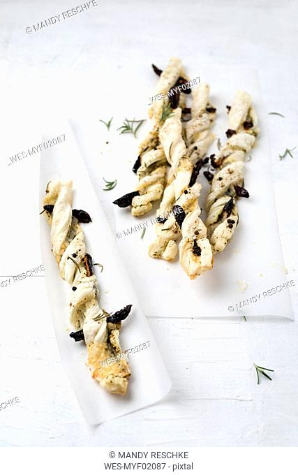 Puff paste sticks with cheese and dried tomato and rosemary