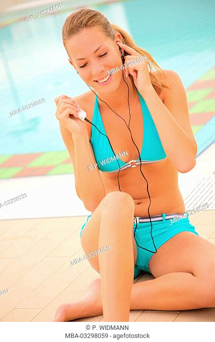 young blond woman hears music with MP3-player in the swimming-pool