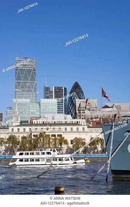 A tourist boat passes the prow of the warship HMS Belfast, docked on the River Thames and part of the Imperial War Museum