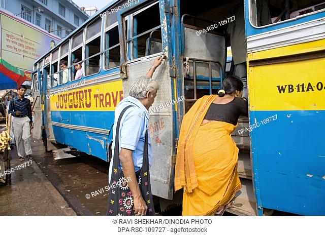 Indian Aged couple boarding on a local bus ; Calcutta Kolkata ; West Bengal ; India
