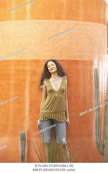 Hispanic woman standing next to cactus, Los Cabos, Mexico