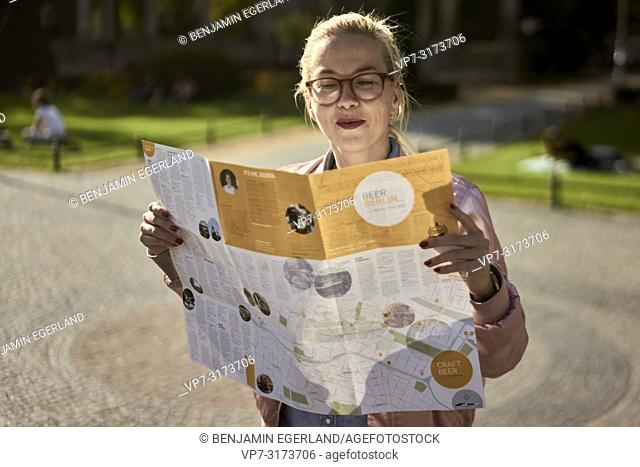 Woman with city guide map, in Berlin, Germany