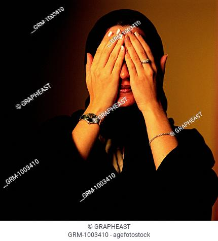 Arab woman covering her eyes with her hands