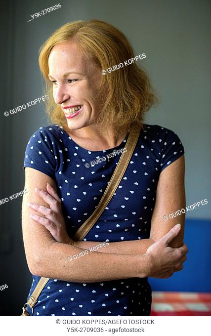 Tilburg, Netherlands. Studio-portrait of happy and smiling red-haired woman