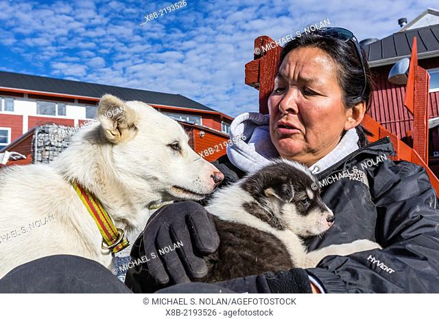 Dog breeder with future sled dog puppies just outside the town of Ilulissat, Greenland