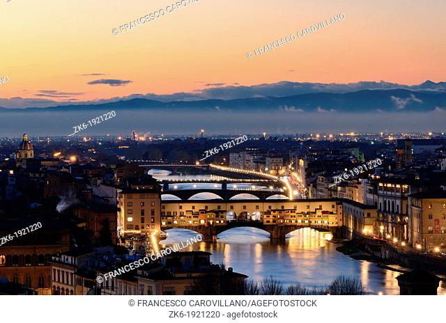 Ponte Vecchio across the Arno river with florence's rooftop around photographed at dusk from an high position