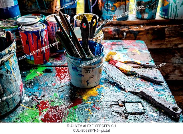 Paint brushes and pots of paints on workshop table
