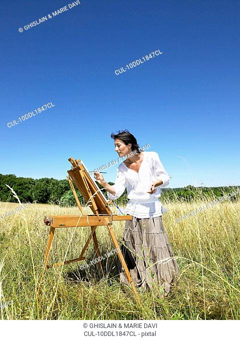 Woman painting in a field, smiling